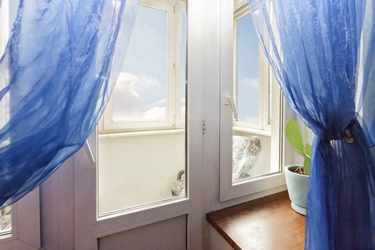 Home window with blue curtain and view to the white cloudy sky
