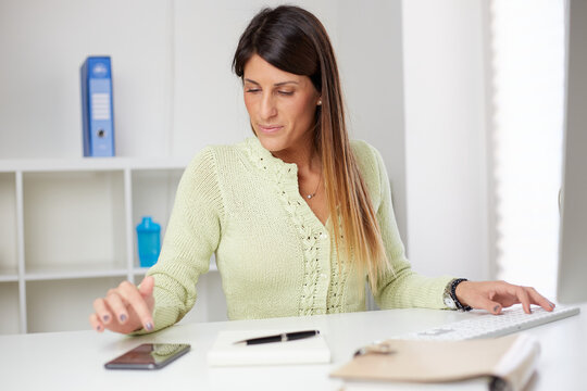 businesswoman typing on smartphone at home office