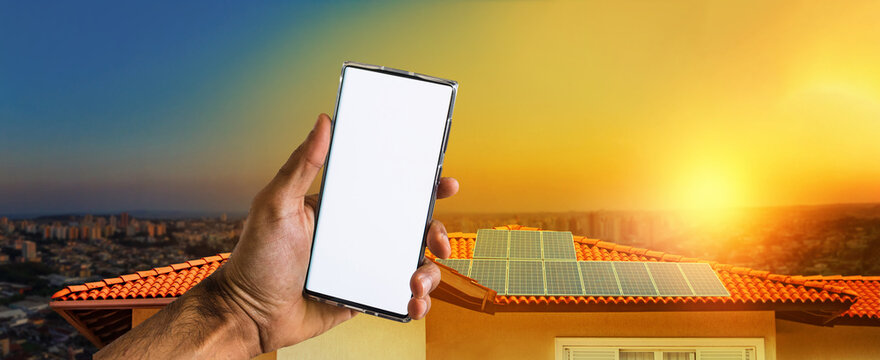 Male hands holding a mobile with solar energy photovoltaic panel at background. Space for text