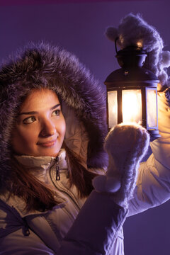 beautiful girl on winter snow with christmas lantern