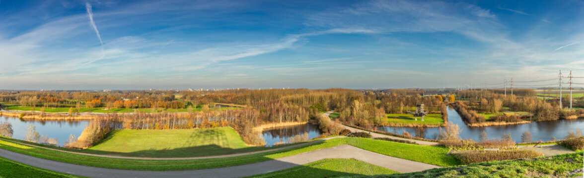Panorama Landscape Park De Groene Weelde as seen from Big Spotters Hill in direction from west to north in bright autumn colors during sunrise against a background blue sky with haze