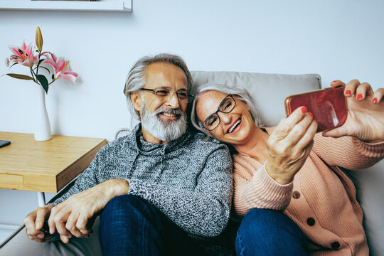 Happy senior couple at home smiling  on couch and looking at mobile phone together