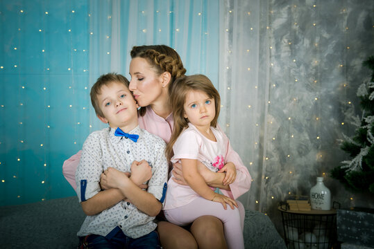 Mom with children at Christmas at home. Happy mother with children. Mom hugs her son and daughter in the bedroom.