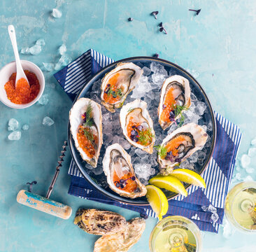 Tasty oysters on ice with lemon. Refined with herbs and salmon caviar.