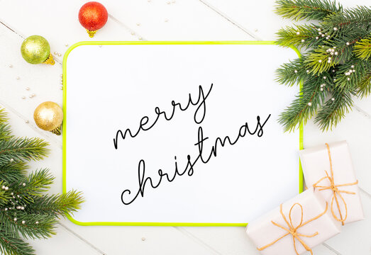 writes merry christmas message on white board with handwriting