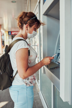 Woman withdrawing money from atm machine using debit or credit card standing outdoors in the street, wearing face mask to cover mouth and nose during pandemic coronavirus outbreak