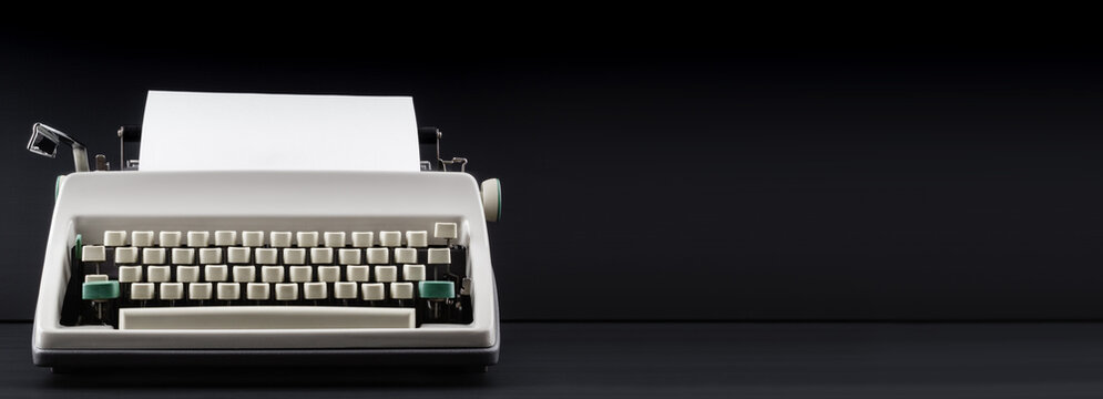 Old retro typewriter with blank paper on black background. Concept of blogging, remote work or freelance. Banner.