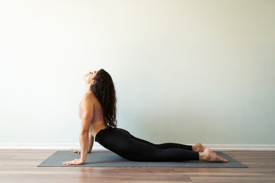 Pretty young woman relaxing her body in a yoga plow pose