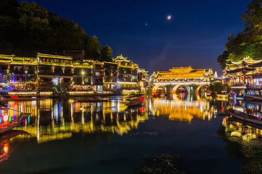 Evening view of riverside houses and Hong bridge in Fenghuang Ancient Town, Hunan province, China