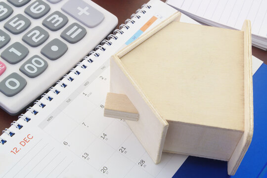 Wooden house on calendar with calculator, Real estate business concept.