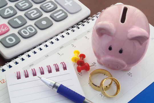 Save money for wedding and planning wedding concept. Piggy bank, wedding rings, push pins, notepad, pen and calculator on calendar.