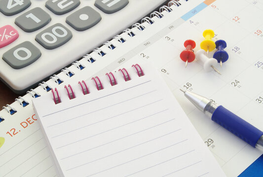 Calculator, notepad, push pins and pen with calendar. Accounting and planning concept.