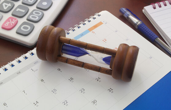 Business time concept, hourglass on calendar with calculator, pen and notepad.