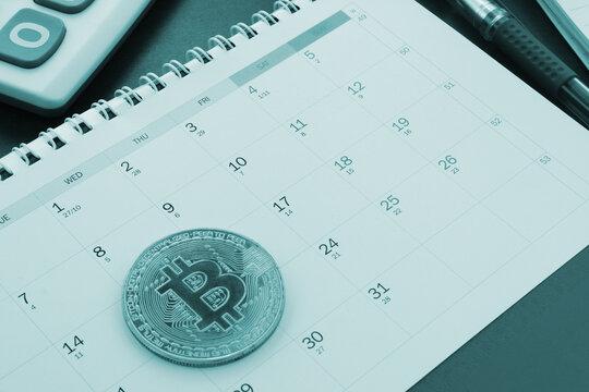 Bitcoins operations concept, bitcoin coin on calendar with calculator.