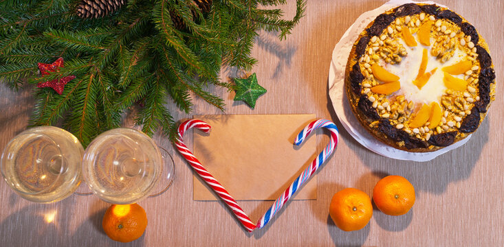 Merry Christmas and Happy New Year. A festive composition with a delicious homemade clock-shaped cake, tangerines, wine glasses by the New Year tree. Space for text on the envelope