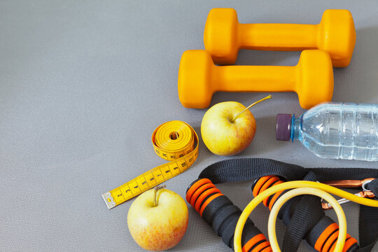 Top view on bright sports equipment, orange dumbbells, yellow rubber expander, bottle of drinking water, apples and measuring tape on a gray gym mat. Sports background. Flat lay, copy space