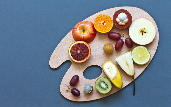 Pieces of vitamin ripe juicy fruits for fruit salad on a cutting board in the form of a palette on a gray-blue table. Edible background. Low-calorie diet. Top view, flat style, copy space, mock up