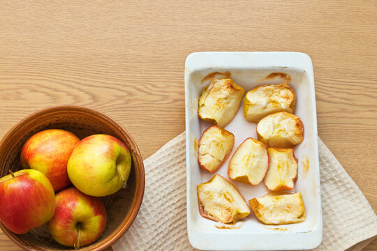 Freshly baked sweet apples in ceramic form on a wooden table. Delicious organic sweets rich in fiber. Digestible food for elderly people, children and people with health problems. Flat lay, copy space