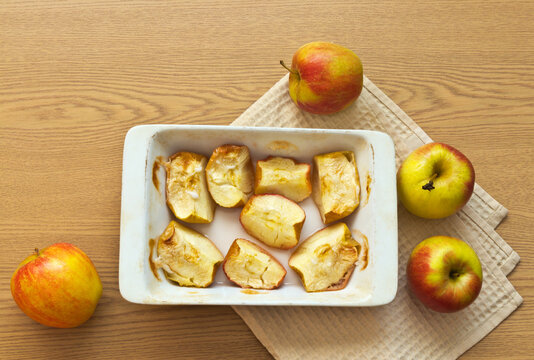 Oven baked slices of sweet apples in a ceramic form and fresh apples on a wooden table. Delicious healthy vegetarian food. Organic products. Flat lay, close-up, copy space, top view