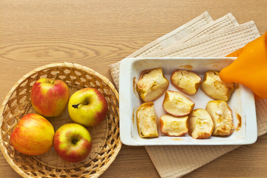 Hot baked in the oven slices of sweet apples in a ceramic form and fresh apples in a wicker basket on a wooden table. Delicious healthy homemade food. Organic products. Flat lay, copy space, close-up