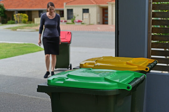Adult woman collecting rubbish bin from road side on rubbish day