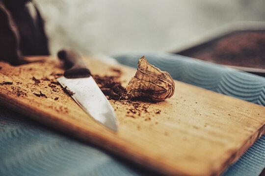 cutting mapacho tobacco on a board.