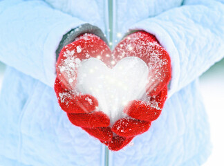 close up of red gloves holding ice heart with glowing sparkles and stars