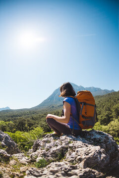 A woman with a backpack sits on top of a mountain and admires the beauty of a mountain valley.