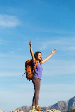 A woman with a backpack stands on top of a mountain and admires the beauty of a mountain valley.