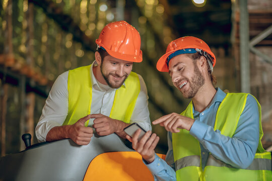 Warehouse worker showing something on his smartphone to the coworker and smiling
