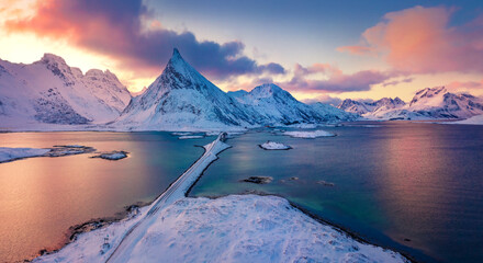 Amazing view from flying drone of Lofoten Islands. Colorful winter sunrise on Norway, Europe. Aerial morning view of Fredvang bridge with Volandstind peak on background.  Life over polar circle.