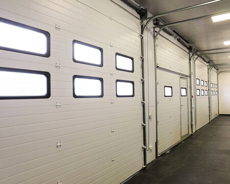 Row of overhead sectional doors in a multi-seat car garage. Inside view.