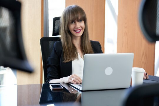 Business portrait - Businesswoman working with laptop computer in corporate office. Young woman smiling.  .
