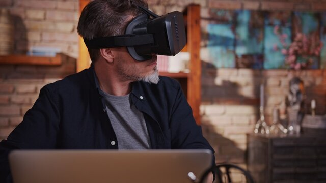 Casual man man playing video game on virtual reality googles at home sitting at desk with laptop computer.
