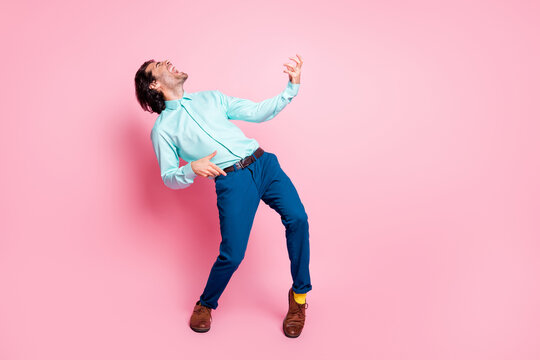 Photo portrait full body view of man playing on air guitar isolated on pastel pink colored background