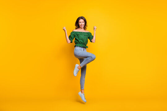 Full body photo of victorious happy woman raise fists yeah jump up wear shoes isolated on shine yellow color background