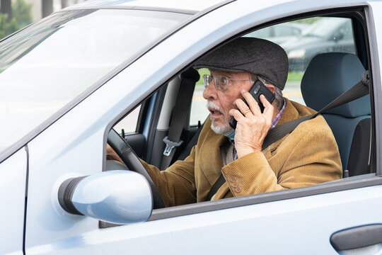 Old man drives his car while talking on mobile phone. Dangerous driving on the road