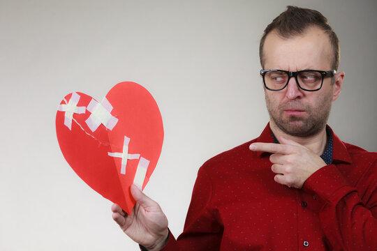 Thoughtful man holds broken heart
