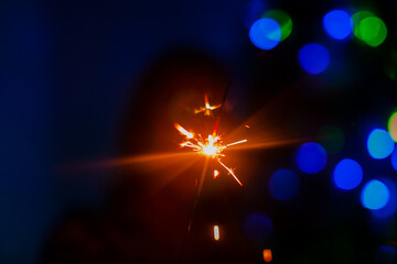 Bright flash of sparkler in the hand of a blurred figure of women