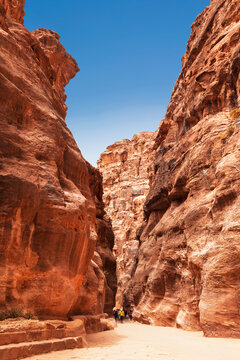 Tourists in narrow passage of rocks of Petra canyon in Jordan. Petra has been a UNESCO World Heritage Site since 1985. Way through Siq gorge to stone city Petra