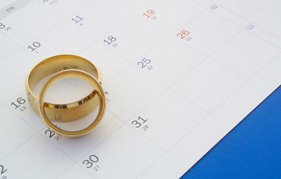 Planning wedding concept. Golden wedding rings on calendar.