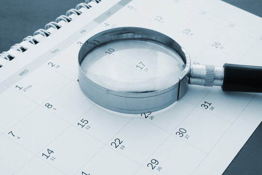 Magnifying glass on calendar close up. Review year events concept.