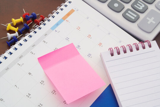 Calculator, notepad, push pins and note paper with calendar. Accounting and planning concept.