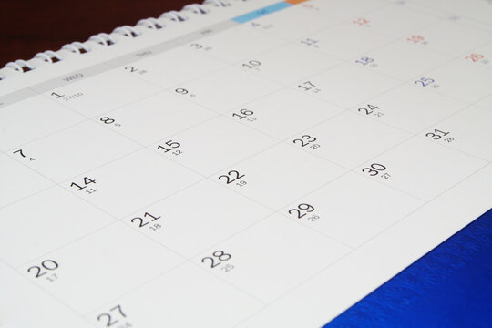 Calendar close up on wooden table. Time and planning concept.