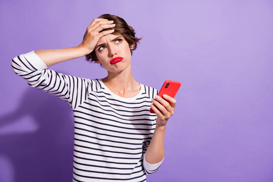 Photo of troubled upset girl hold cellphone palm brow look empty space wear striped shirt isolated purple color background