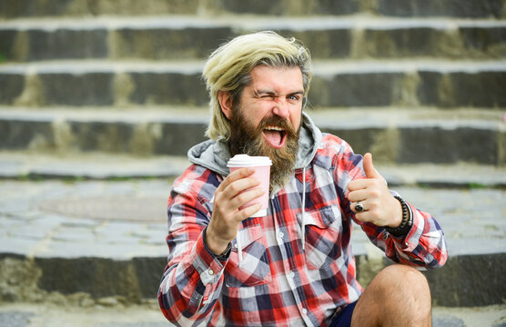 Pure pleasure. Hipster relax on stairs. Having rest. Caffeine dose. Good mood. Bearded man drink coffee urban background. Take away coffee. Third wave coffee culture. Man with beard drinking coffee