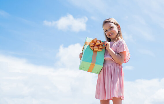 little kid with gift box. happy birthday party. childhood happiness. lets celebrate holiday. child in summer day on sky background. its shopping time. small girl hold present box. copy space