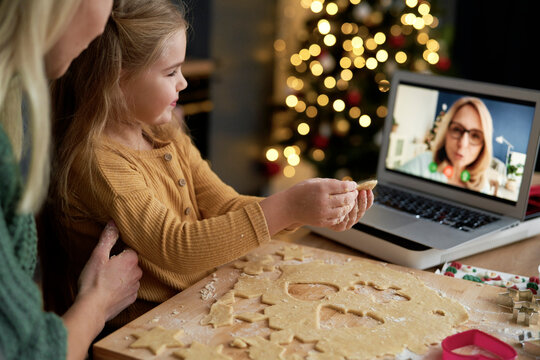 Granddaughter showing her grandma Christmas cookies during a video conference