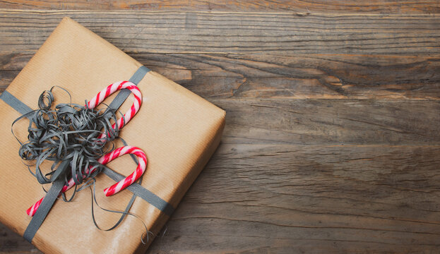 Brown gift box with ribbon and candy cane on wooden background.