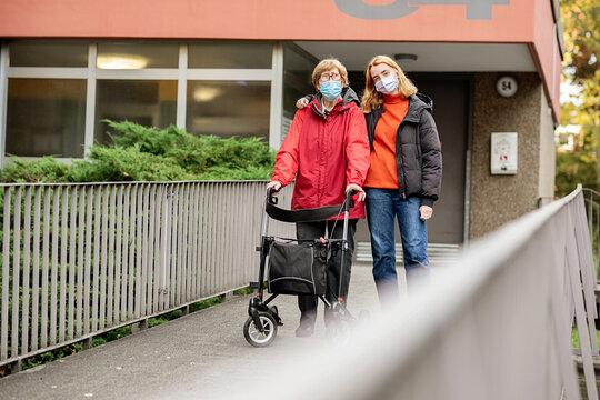 Seniorin und Enkelin zu Besuch unterhalten sich vor Seniorenheim mit Make zum Schutz vor Corona Virus